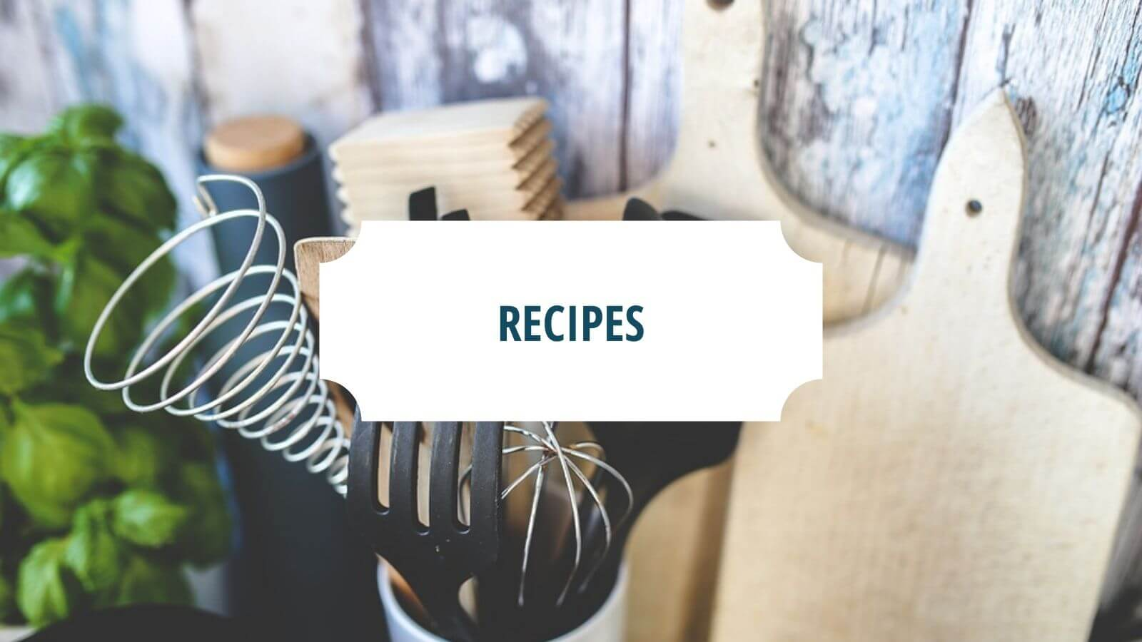 """Kitchen utensils with the word """"recipes"""" in green on a white block 
