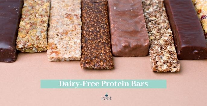 """Chocolate and nut protein bars lined up on a pink background with the words """"dairy free protein bars"""" in white writing against a turquoise banner 