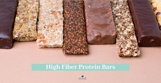 """Chocolate and nut protein bars lined up on a pink background with the words """"high fiber protein bars"""" in white writing against a turquoise banner 